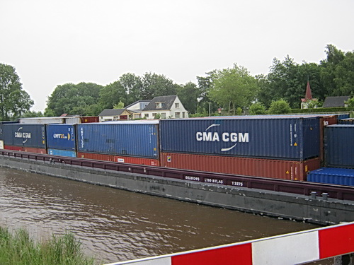 Bij de brug tussen Noord- en Zuidhorn is te zien waarom de vaarweg Lemmer-Delfzijl dient te worden verruimd: Een containerschip van 3275 vaart westwaarts. Lengte 110 meter! (En ik heb er al eens eentje van 3297 t. gezien...)