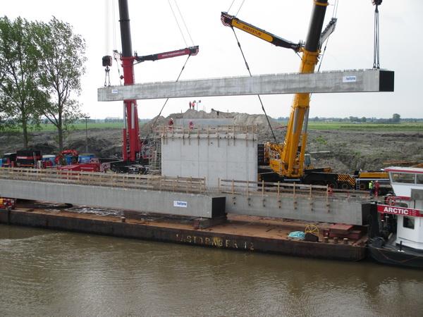 De eerste korte ligger wordt behoedzaam op zijn plaats gelegd, tussen pijler en landhoofden aan de zuidkant van de NVH-brug