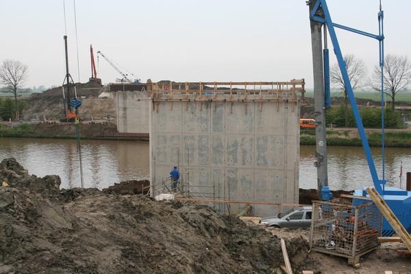 Foto vanaf de zuidkant van de bouwput van de nieuwe, vaste, hoge brug. Beide pijlers zijn al zonder bekisting. Aan de landhoofden wordt nog gewerkt.